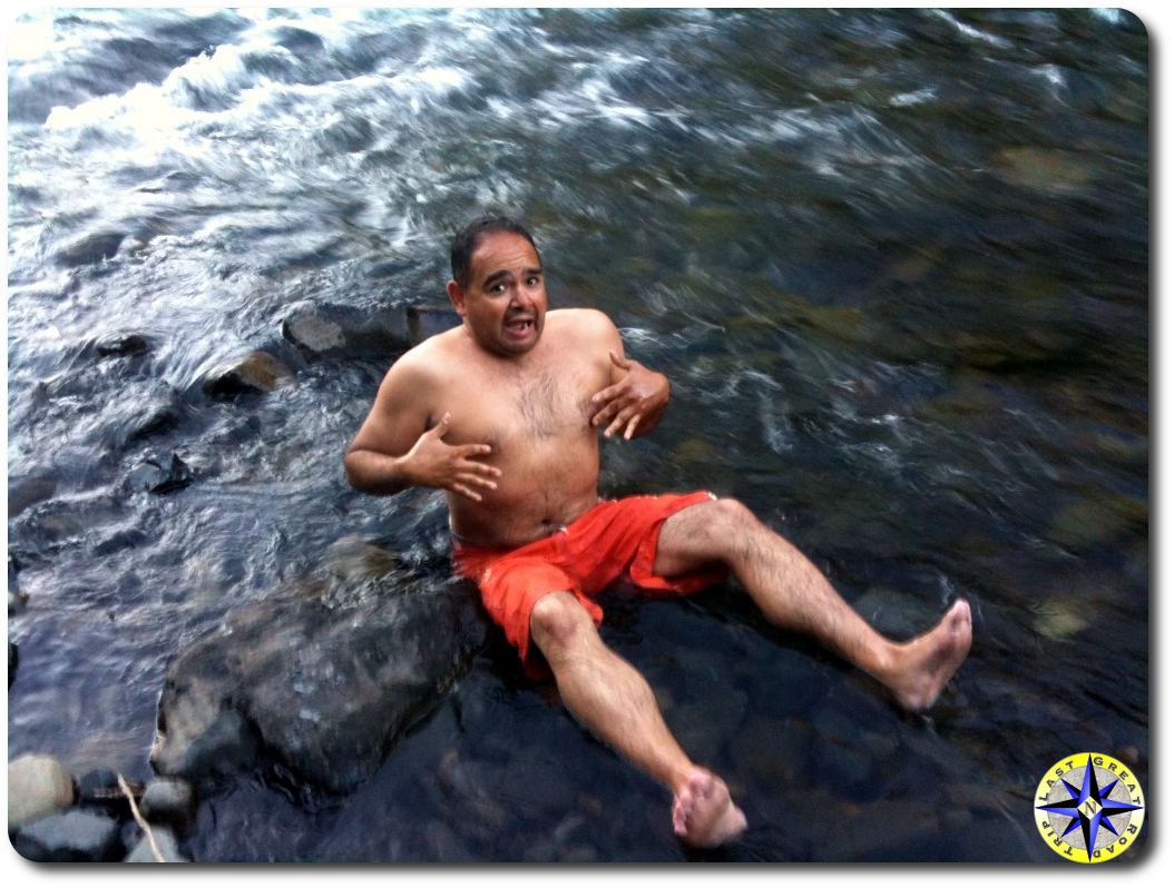 man sitting in cold river water