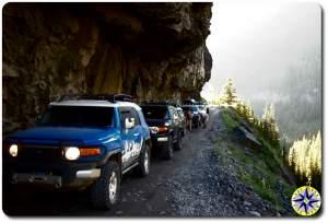 fj cruisers under rock ledge