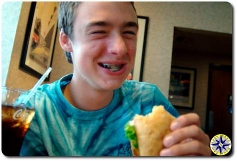 laughing boy eating sandwitch