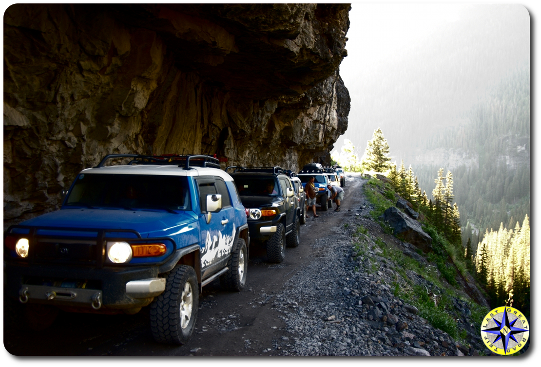 fj cruisers under rock ledge