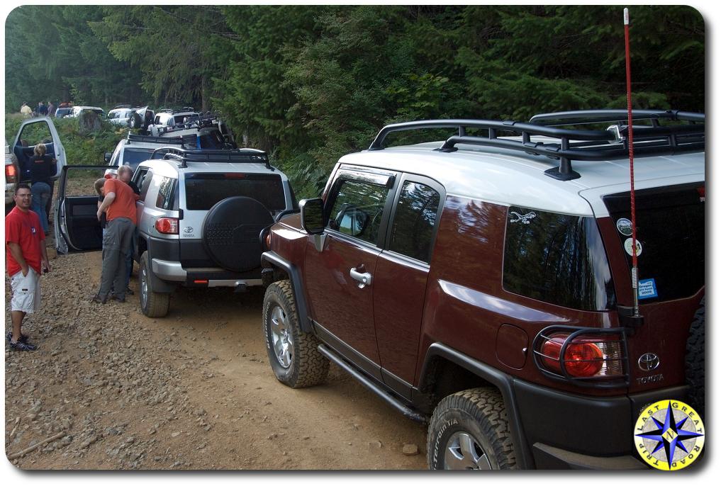 fj cruisers backed up on 4x4 trail