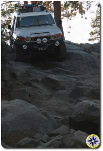 fj cruiser decending steep rock face rubicon trail