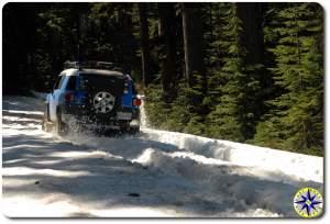 voodoo blue fj cruiser driving through snow 4x4 trail