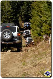 four fj cruisers on 4x4 trail
