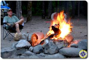 man sitting by camp fire