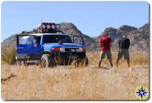 men peeing side of dirt road next to fj cruiser