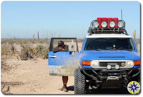 man resting against fj cruiser door mexico