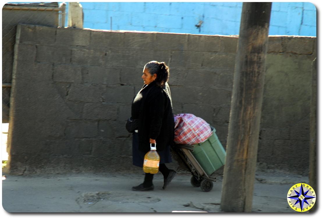 tijauna woman walking by brick wall
