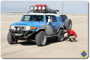 man airing down fj cruiser tire baja mexico