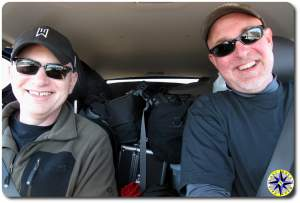 two men smiling in fj cruiser packed with gear