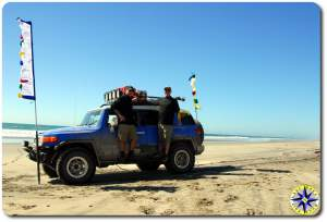 two men standing on fj cruiser baja mexico pacific beach prayer flags