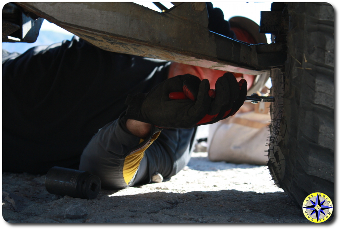 man inspecting truck suspension in sand