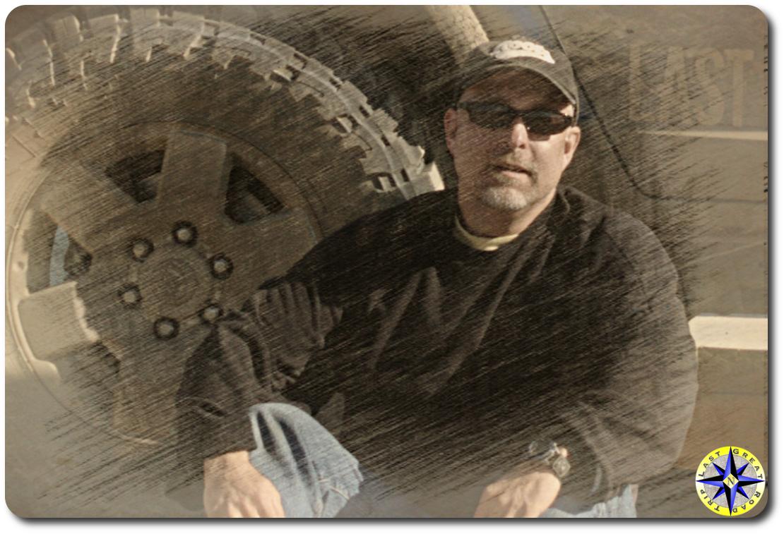 paul sketch man sitting next to truck tire