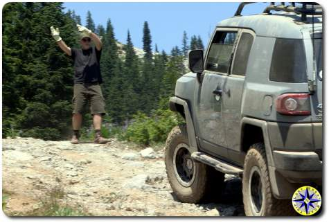 man spotting fj cruiser on trail