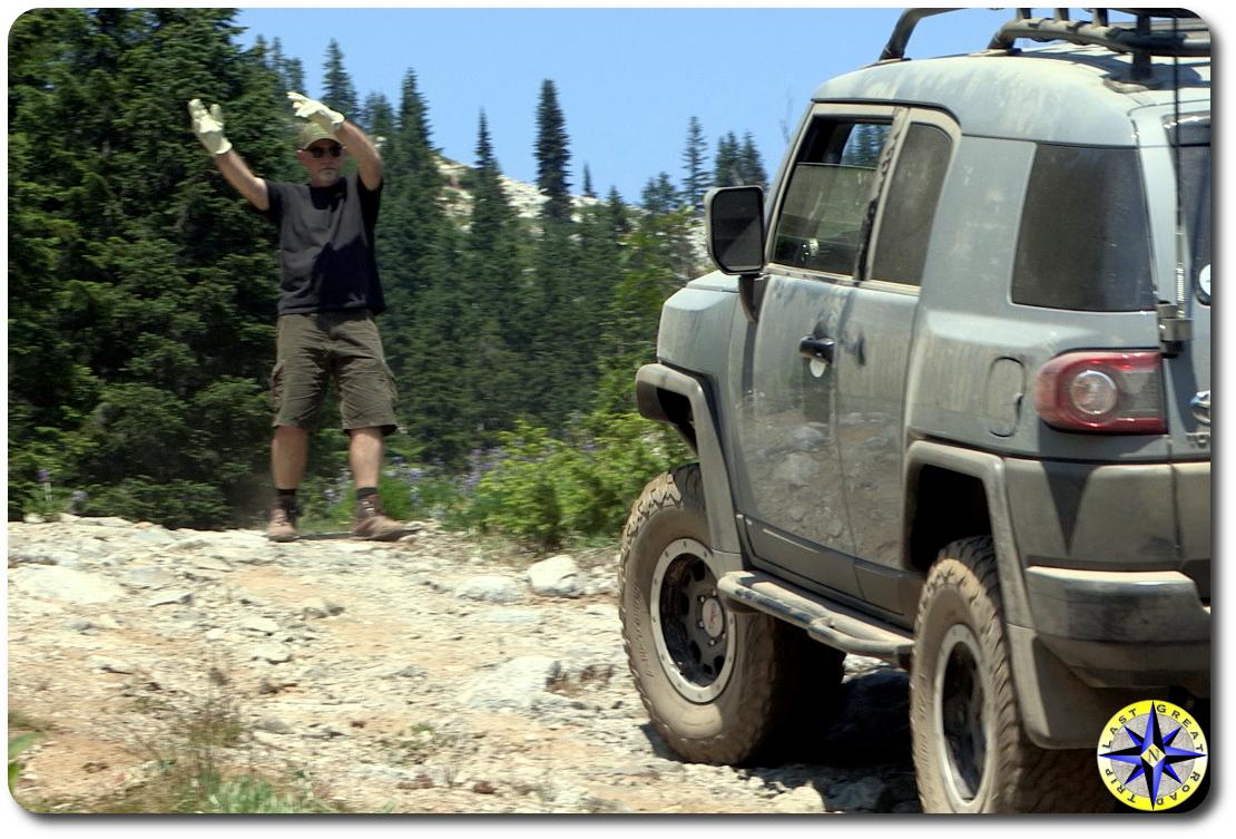 man spotting fj cruiser on trail