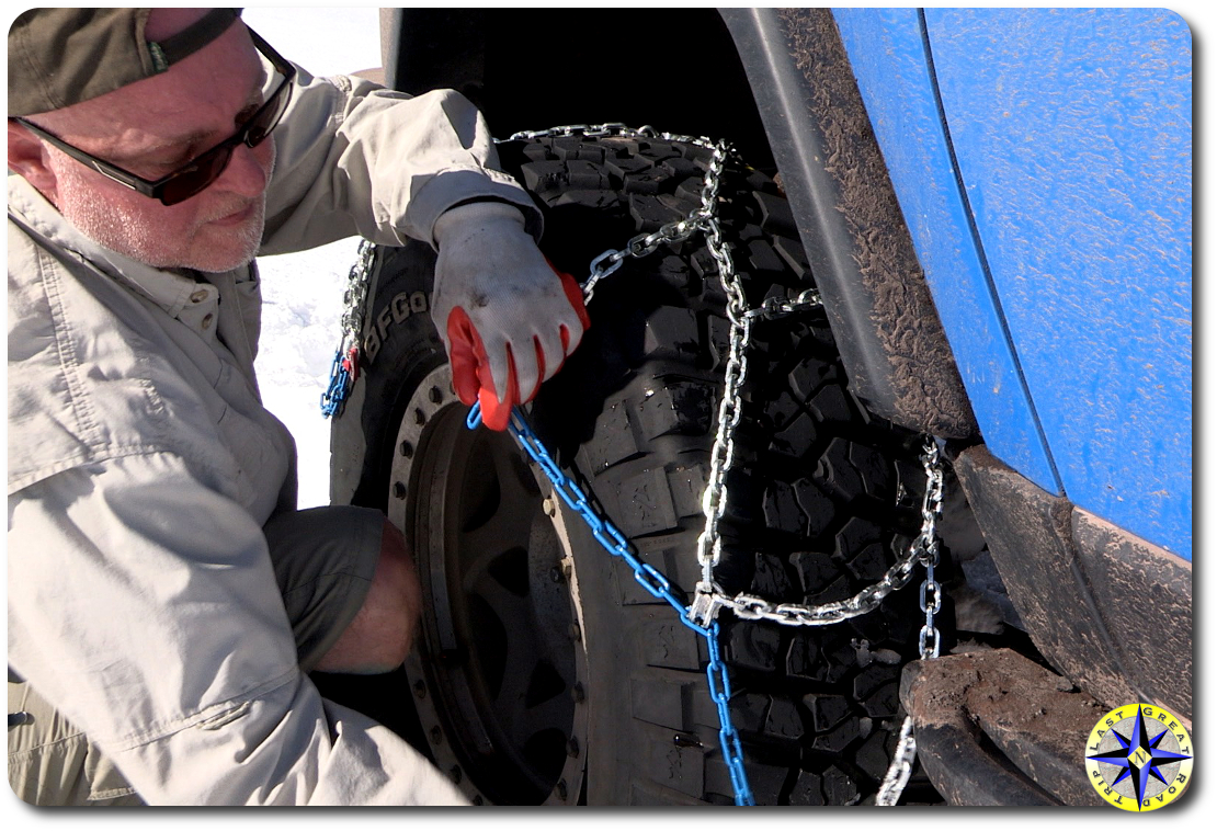 man putting on tire chains