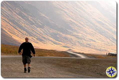 man hiking haul road