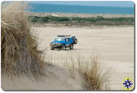 fj cruiser sitting in sand dunes