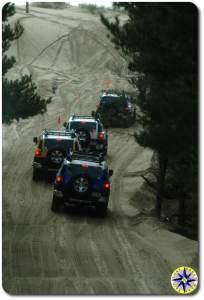 fj cruisers in a row on sand dune trail