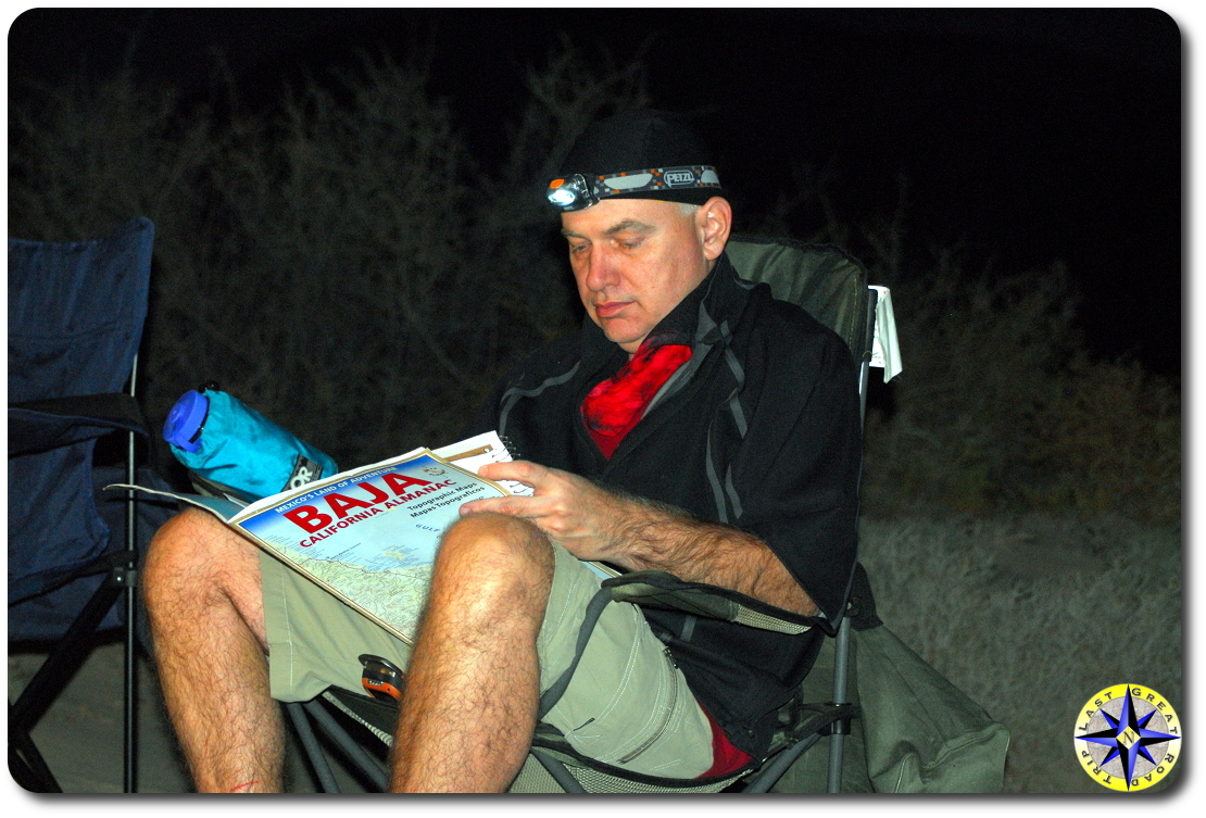 man in camp chair studying baja map