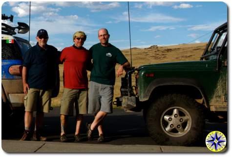 three men in front of trucks