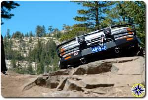 FJ 80 peaking over rock