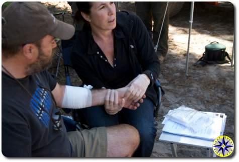 woman taking injured man pulse
