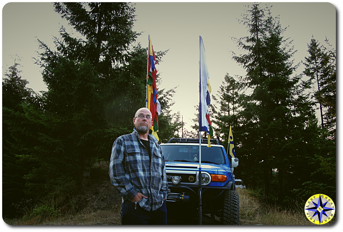 man in front of FJ Cruiser with prayer flags