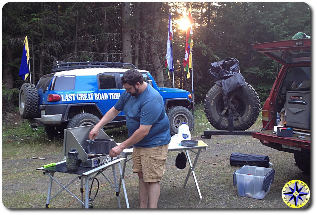 man cooking camp stove